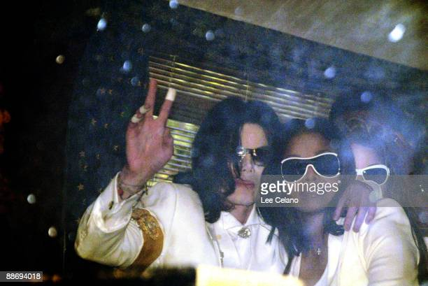 Michael Jackson waves to fans with his his sister Janet Jackson from inside the family bus as they leave for lunch break during a pretrial hearing on...