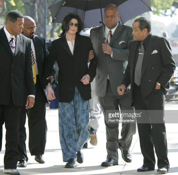 Michael Jackson wears pajama pants and is aided by bodyguards as he arrives more than an hour late with his father Joe Jackson for his child...