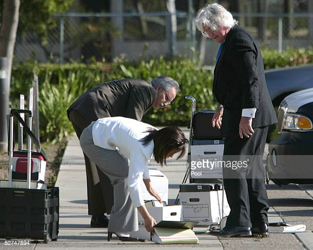 Michael Jackson's defense team members Thomas Mesereau Jr Susan Yu and Scott Ross pick up files on the sidewalk in front of the Santa Barbara County...