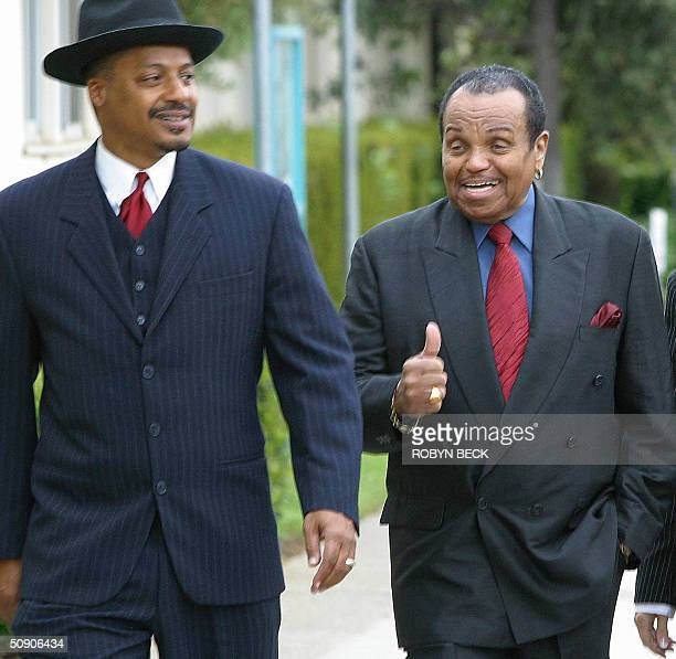 Michael Jackson's father Joe Jackson gives the thumbs up as he arrives with family spokesman Firpo Carr for his son's pretrial hearing 28 May 2004 at...