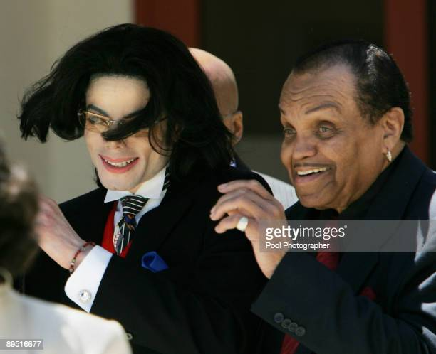 Michael Jackson's hair flies in the wind as he departs with his father Joe Jackson from the Santa Barbara County courthouse April 29 in Santa Maria...