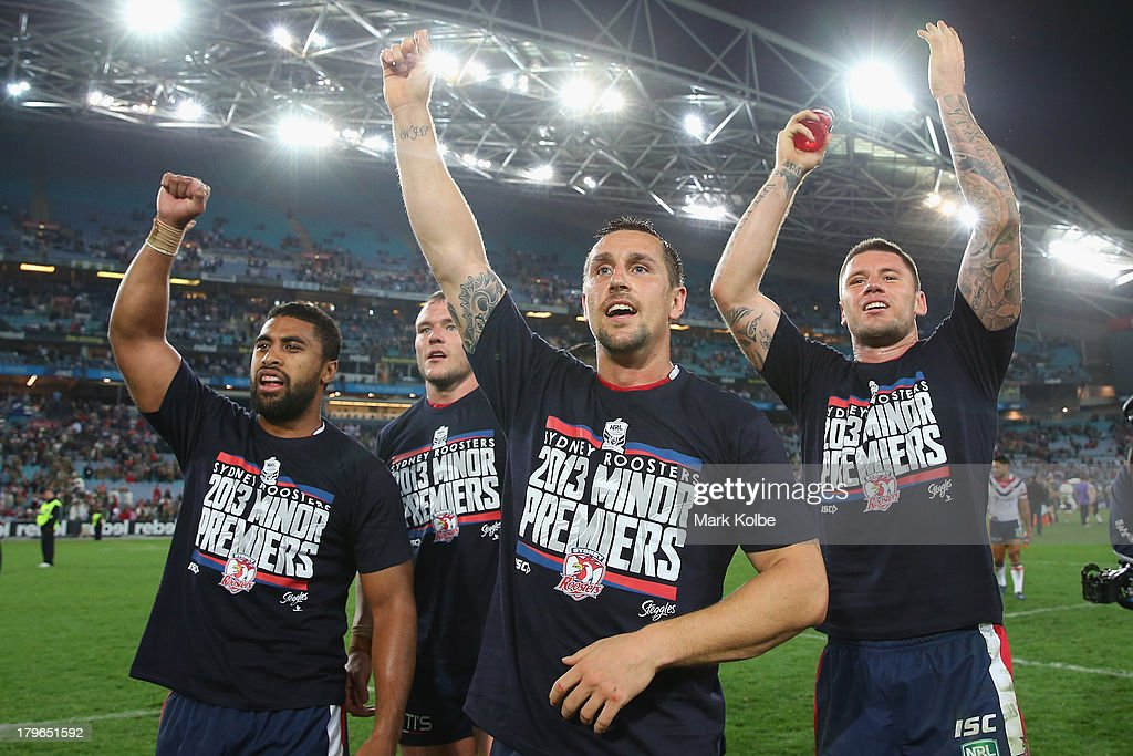 Michael Jennings, Mitchell Pearce and Shaun Kenny-Dowall of the Roosters wear 2013 Minor Premiership T-shirt as they celebrate victory during the round 26 NRL match between the South Sydney Rabbitohs and the Sydney Roosters at ANZ Stadium on September 6, 2013 in Sydney, Australia.