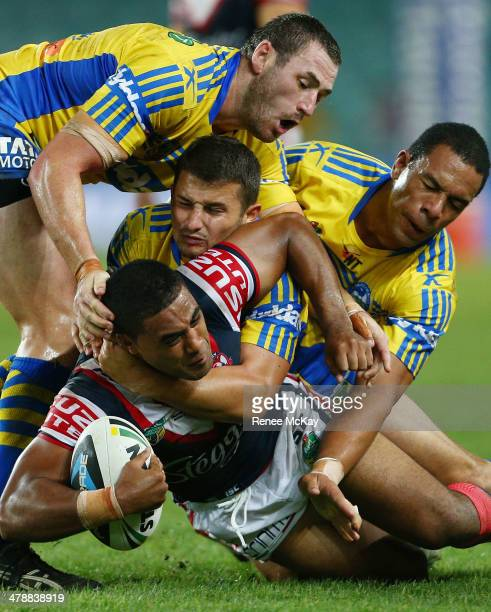 Michael Jennings of the Roosters is tackled by Luke Kelly, Ben Smith and Will Hopoate during the round two NRL match between the Sydney Roosters and...