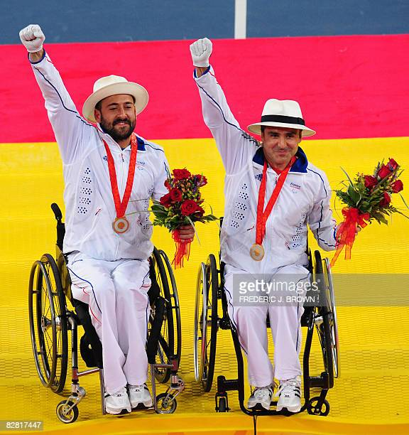 Michael Jeremiasz and Stephane Houdet of France salute the crowd after receiving their gold medals following their victory over Sweden's Stefan...