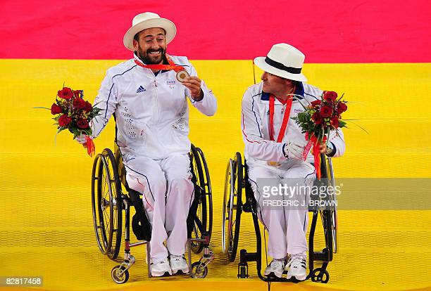 Michael Jeremiasz of France holds his gold medal as partner Stephane Houdet looks on after receiving their medals following their victory over...