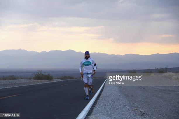 Michael Jimenez runs with a member of his support crew during the STYR Labs Badwater 135 on July 12 2017 in Death Valley California The start of the...