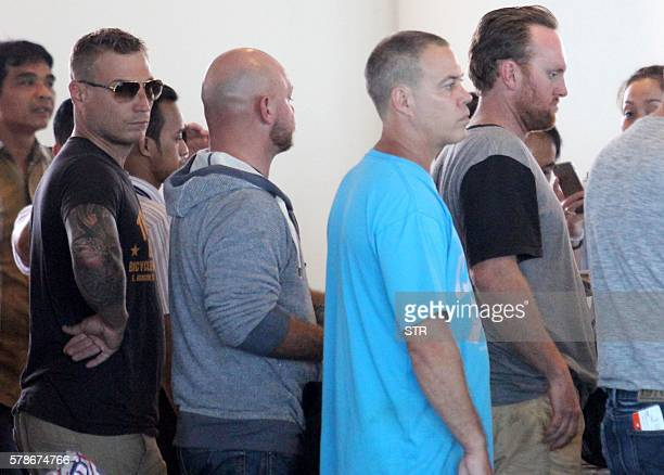 Michael John Matttews Ricky William Longmuir and Mark Paul Eric Rossiter of Australia stand in a queue to board a flight at Ngurah Rai Airport in...