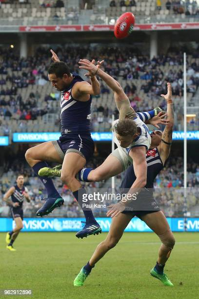 Michael Johnson and Michael Walters of the Dockers contest a mark against Jack Ziebell of the Kangaroos during the round 10 AFL match between the...