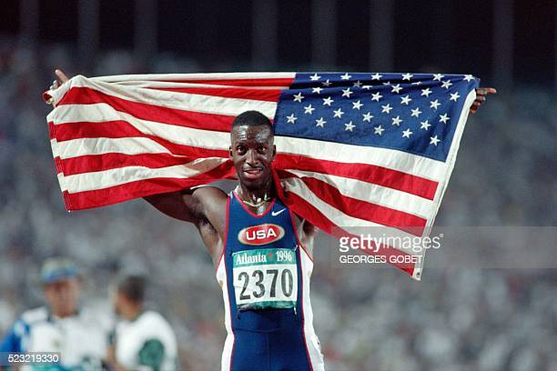 Michael Johnson displays the US flag after winning the men's 400m final in 43.49sec, at the athletics event during the Atlanta 1996 Olympic Games on...