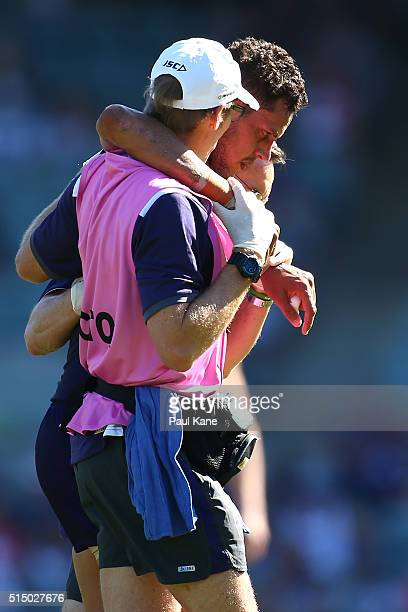 Michael Johnson of the Dockers is assisted from the field after being tackled by Nakia Cockatoo of the Cats during the NAB Challenge match between...