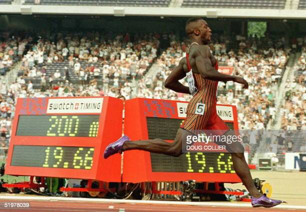 Michael Johnson of the US runs past the clock after crossing the finish line to win the men's 200 meter final 23 June at the US Track and Field...