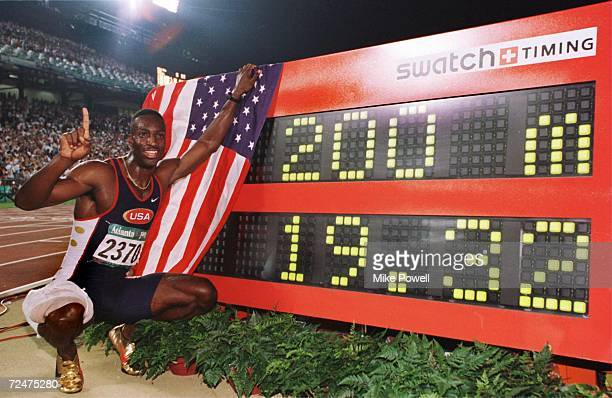 Michael Johnson of the USA poses next to his new world record time of 19.32 seconds in the men's 200 meters during Centennial Olympic Games at...