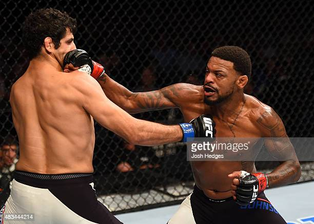 Michael Johnson punches Beneil Dariush in their lightweight bout during the UFC Fight Night event at Bridgestone Arena on August 8 2015 in Nashville...