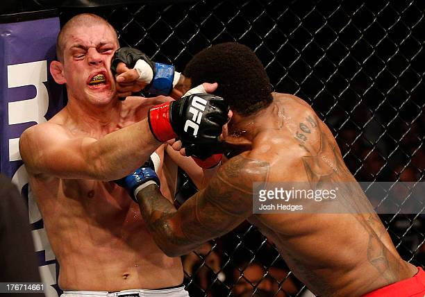 Michael Johnson punches Joe Lauzon in their UFC lightweight bout at TD Garden on August 17, 2013 in Boston, Massachusetts.