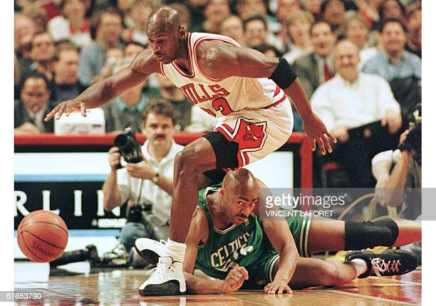 Michael Jordan a guard for the Chicago Bulls steps over Boston Celtics forward Alton Lister to recover a loose ball in the first half of their 01...