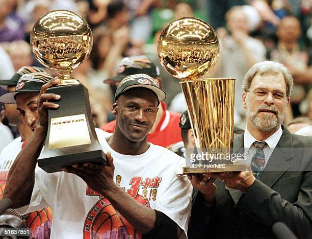 Michael Jordan and Chicago Bulls head coach Phil Jackson Most Valuable Player trophy and the Larry O'Brian trophy 14 June after winning game six of...
