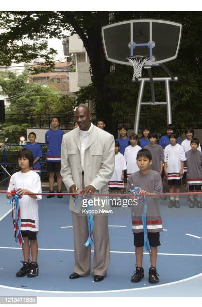 Michael Jordan attends a tapecutting ceremony to mark his donation of a basketball court at Mitake Park in Tokyo's Shibuya on May 23 2004