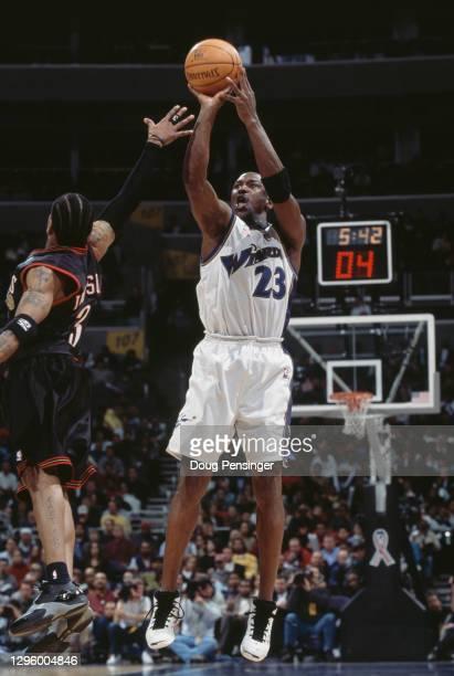 Michael Jordan for the Washington Wizards makes a jump shot as Allen Iverson of the Philadelphia 76ers reaches to block during their NBA Atlantic...