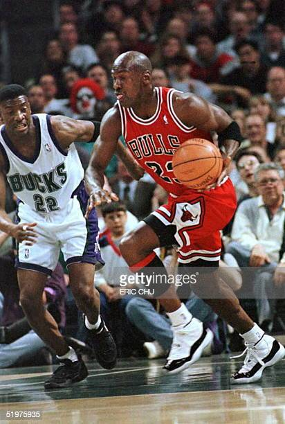 Michael Jordan , guard for the Chicago Bulls, drives past Milwaukee Bucks guard Johnny Newman during the first quarter action 16 April in Milwaukee,...
