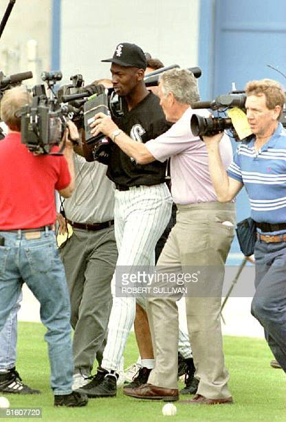 Michael Jordan is surrounded by reporters 16 February 1994 in Sarasota FL as he makes his way to the practice field for spring training with the...