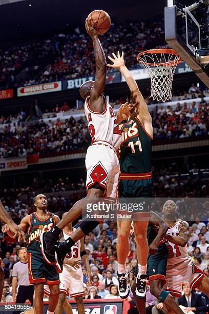 Michael Jordan of the Chicago Bulls attempts a dunk against Detlef Schrempf of the Seattle SuperSonics during Game Six of the 1996 NBA Finals at the...