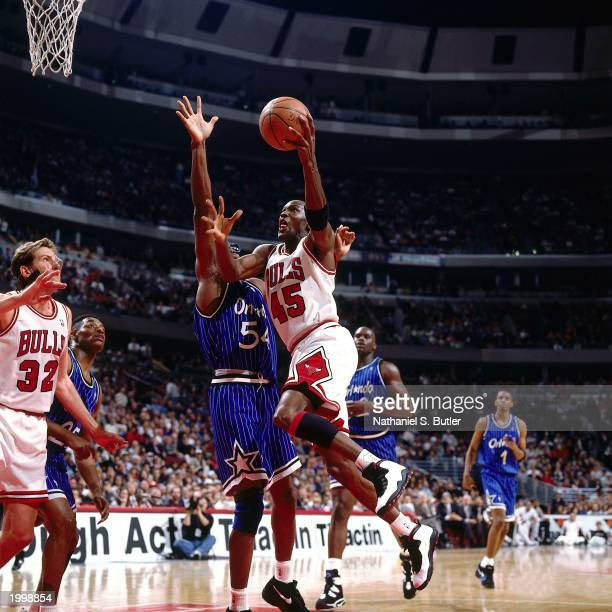 Michael Jordan of the Chicago Bulls attempts a layup against Horace Grant of the Orlando Magic during the NBA game at the United Center on March 24...
