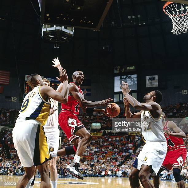 Michael Jordan of the Chicago Bulls attempts a shot against Dale Davis of the Indiana Pacers during the NBA game at Market Square Arena on March 19...