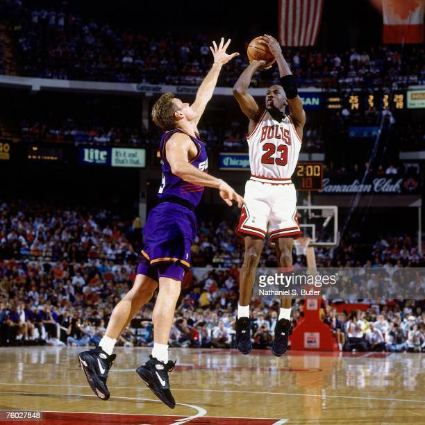 Michael Jordan of the Chicago Bulls attempts a shot against Dan Majerle of the Phoenix Suns in Game Five of the 1993 NBA Finals on June 18 1993 at...