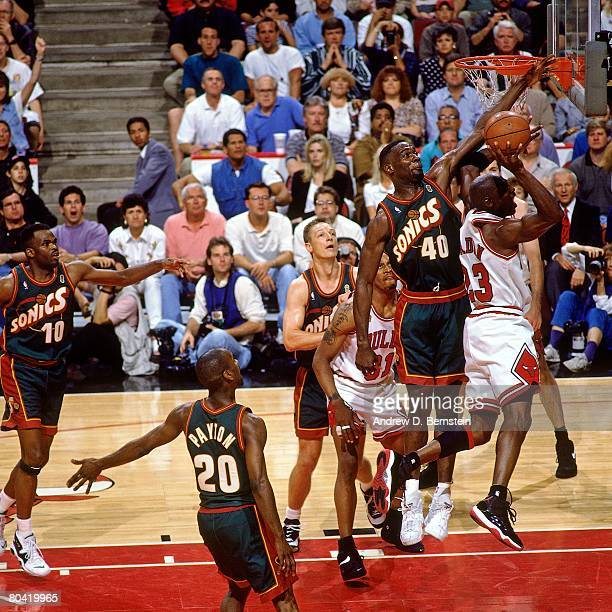Michael Jordan of the Chicago Bulls attempts a shot against Shawn Kemp of the Seattle SuperSonics during Game Six of the 1996 NBA Finals at the...