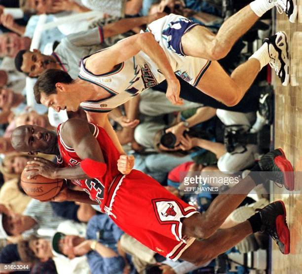 Michael Jordan of the Chicago Bulls backs into Jeff Hornacek of the Utah Jazz 11 June during the second half of game five of the 1997 NBA Finals at...