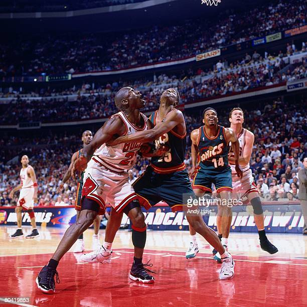 Michael Jordan of the Chicago Bulls battles for a rebound against David Wingate of the Seattle SuperSonics during Game Six of the 1996 NBA Finals at...
