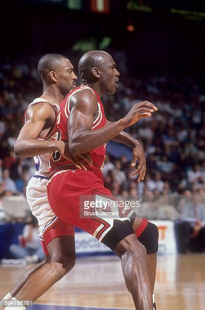 Michael Jordan of the Chicago Bulls battles with Hersey Hawkins of the Philadelphia 76ers during a game in the 1991 Eastern Conference Semifinals in...