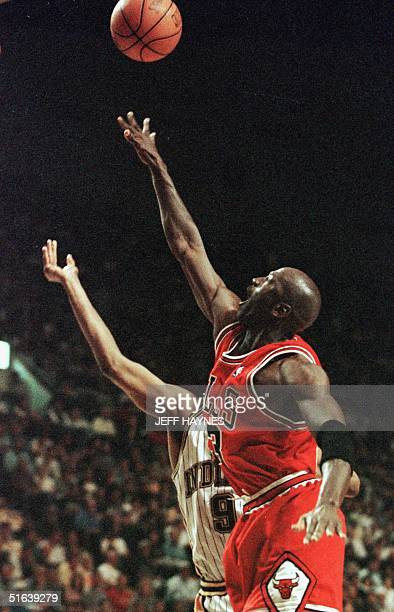 Michael Jordan of the Chicago Bulls blocks the shot of Derrick McKey of the Indiana Pacers 23 May during the first half of game three of their NBA...