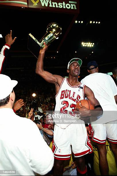 Michael Jordan of the Chicago Bulls celebrates with the Championship trophy after winning the 1992 NBA Finals against the Portland Trail Blazers NOTE...