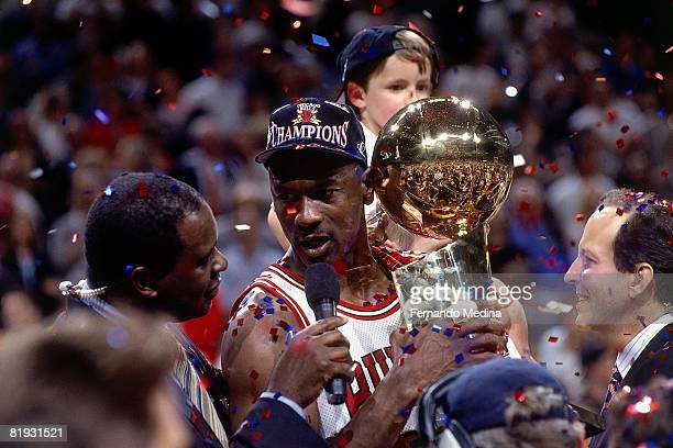 Michael Jordan of the Chicago Bulls celebrates with the championship trophy after defeating the Utah Jazz in Game six of the 1997 NBA Finals at the...