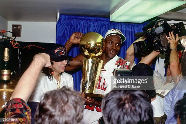Michael Jordan of the Chicago Bulls celebrates with the Larry O'Brien trophy after defeating the Portland Trailblazers in Game six of the NBA Finals...