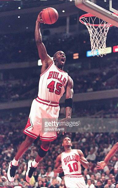 Michael Jordan of the Chicago Bulls cuts through traffic to dunk the ball in the third quarter 20 April against the Detroit Pistons at the United...