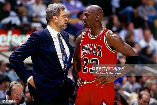 Michael Jordan of the Chicago Bulls discusses strategy with head coach Phil Jackson in Game Six of the 1996 NBA Finals against the Seattle...