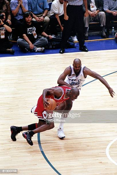 Michael Jordan of the Chicago Bulls dribbles past Bryon Russell of the Utah Jazz prior to shooting the game winning jumpshot during game six of the...