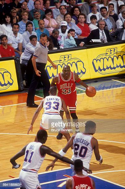Michael Jordan of the Chicago Bulls dribbles the ball as he is defended by Hersey Hawkins of the Philadelphia 76ers duing a game in the 1991 Eastern...