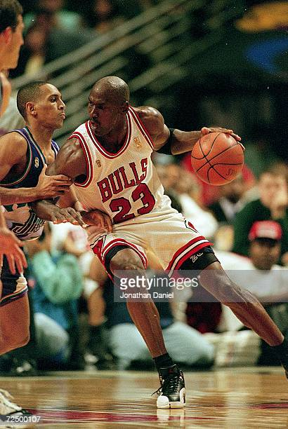 Michael Jordan of the Chicago Bulls dribbles the ball as he is guarded by Howard Eisley of the Utah Jazz during the NBA Final game at the United...