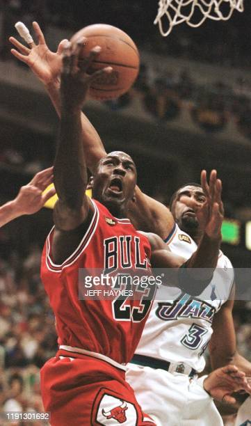 Michael Jordan of the Chicago Bulls drive in the lane past Chris Morris of the Utah Jazz 14 June during game six of the NBA Finals at the Delta...