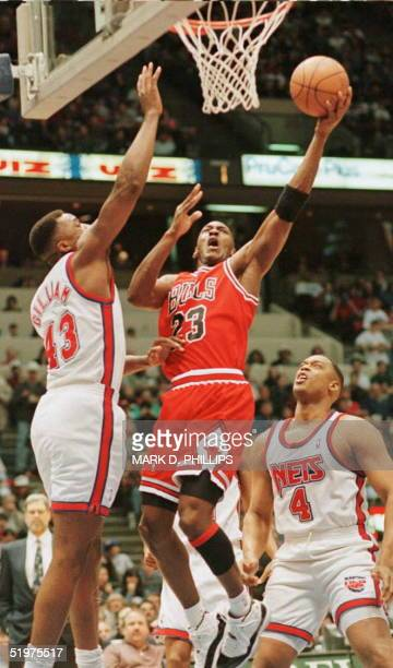 Michael Jordan of the Chicago Bulls drives for a layup between New Jersey Nets Armon Gilliam and Rick Mahorn to score two of his 27 first-half points...
