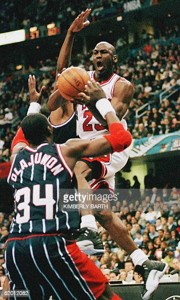 Michael Jordan of the Chicago Bulls drives to the basket as Hakeem Olajuwon of the Houston Rockets guards during the first half of the NBA AllStar...