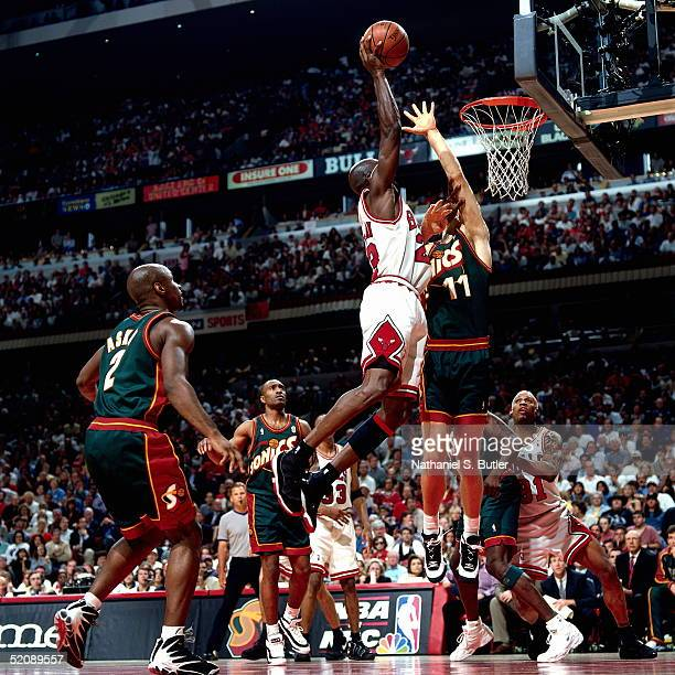 Michael Jordan of the Chicago Bulls drives to the basket for a shot over the outstretched arms of Detlef Schrempf of the Seattle Sonics during Game...
