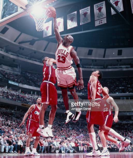 Michael Jordan of the Chicago Bulls dunks the ball over James Collins, Keith Closs Jr. #33 and Eric Piatkowski of the Los Angeles Clipper at the...