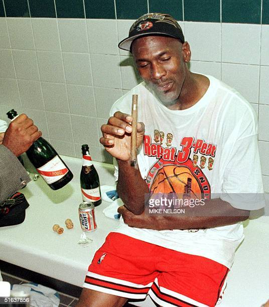 Michael Jordan of the Chicago Bulls enjoys a cigar in the locker room 14 June after winning game six of the NBA Finals against the Utah Jazz at the...