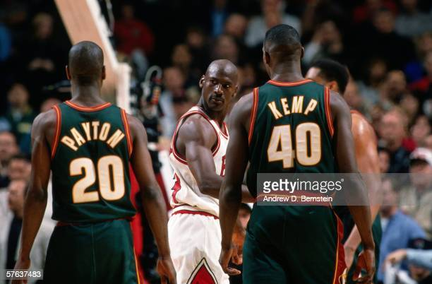 Michael Jordan of the Chicago Bulls glances at Gary Payton and Shawn Kemp of the Seattle SuperSonics during Game Two of the NBA Finals at the United...