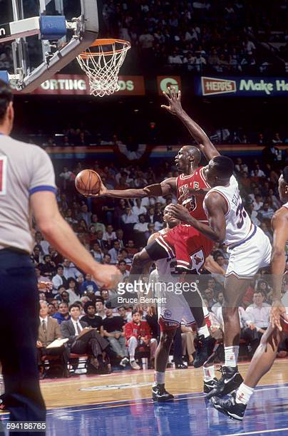 Michael Jordan of the Chicago Bulls goes for the layup against Armen Gilliam and Charles Barkley of the Philadelphia 76ers during a game in the 1991...