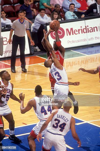 Michael Jordan of the Chicago Bulls goes for the shot as he is defended by Hersey Hawkins of the Philadelphia 76ers duing a game in the 1991 Eastern...